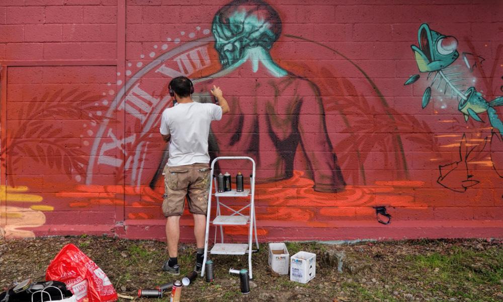 Un graffeur réalise un graff sur un site Urbex